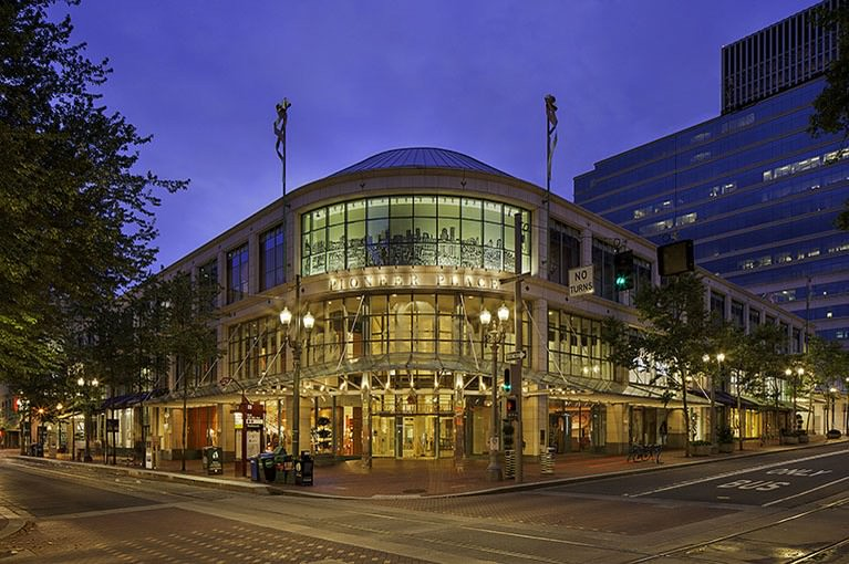 At dusk, the exterior entrance of Pioneer Place is illuminated as light pours out through the skylights.